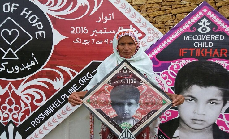 60-year-old Ameeran Bibi holding kite with photo of her grand daughter Rafia who went missing in Sep