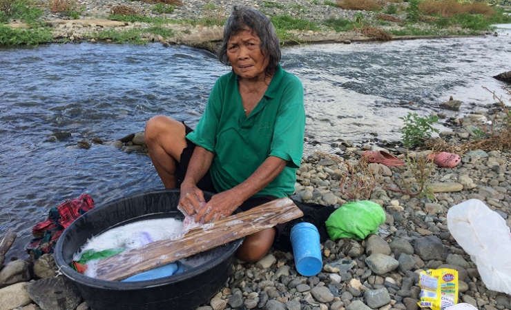Elisa Hernandez washes clothes on the bank of the Boac river (Photo: Jason Strother)