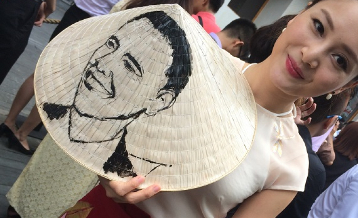 Stage actress Lan Phuong sketched President Obama's face onto a traditional Vietnamese hat to greet