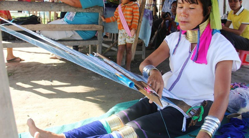 Kayan women is sewing traditional dresses to sell visitors. (Photo: Phyu Zin Poe)