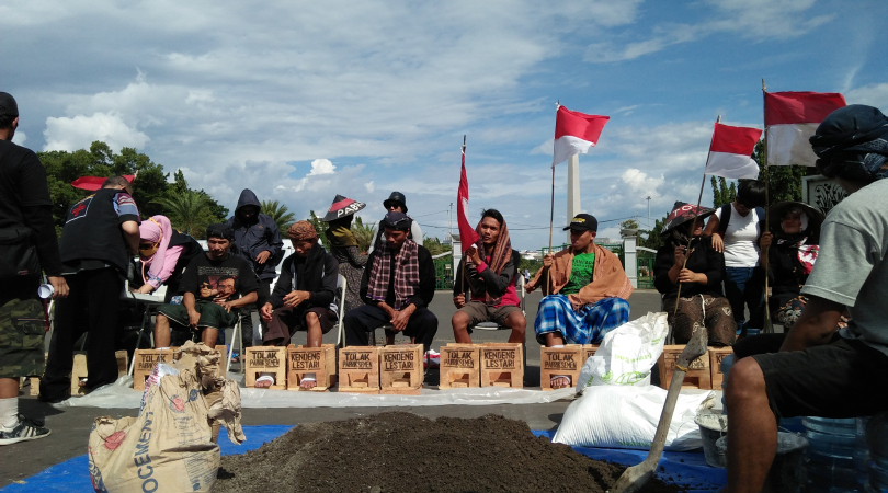 Farmers from central Java cement their feet in protest of a cement factory being established, which