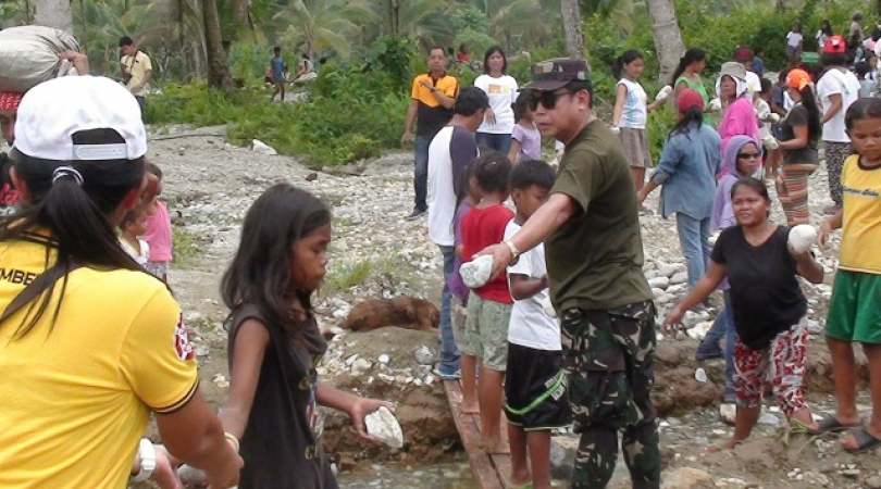 Children help rebuild their school which was buried by flash floods and mud during a typhoon (Photo: